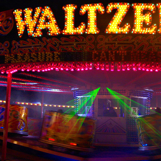 Waltzer ride lit up at a funfair